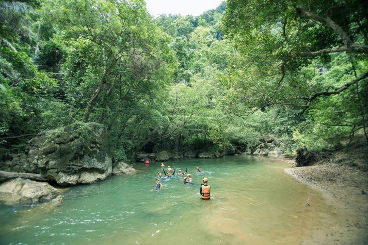Để đến được hang Tổ Mộ, du khách phải bơi qua con sông xanh biếc tại thung lũng Tổ Mộ.