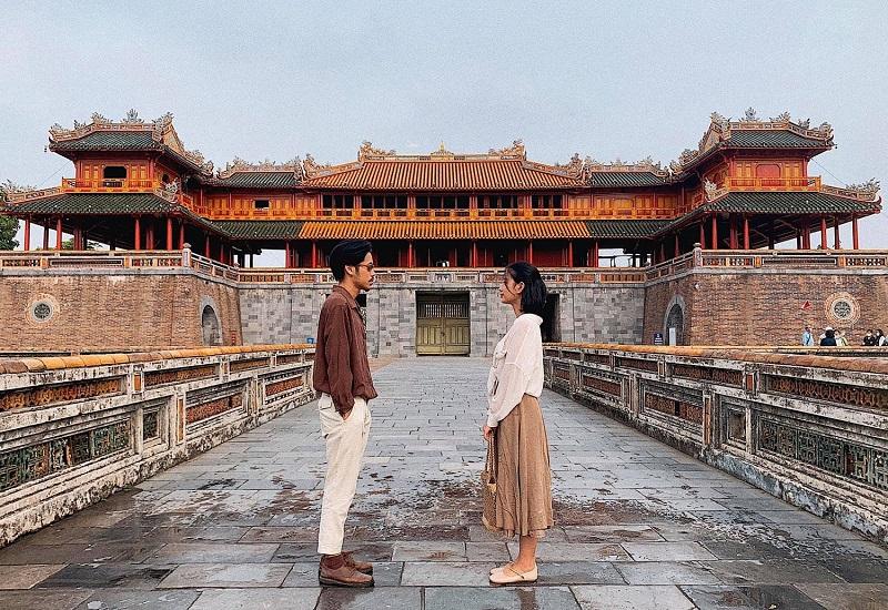Hai bạn trẻ đang đứng trước cổng Ngọ Môn kinh thành Huế