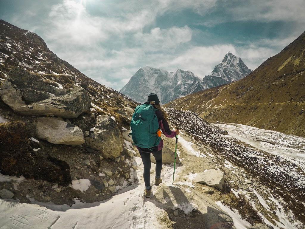 người phụ nữ đeo balo xanh sử dụng gậy leo núi để di chuyển địa hình núi đá