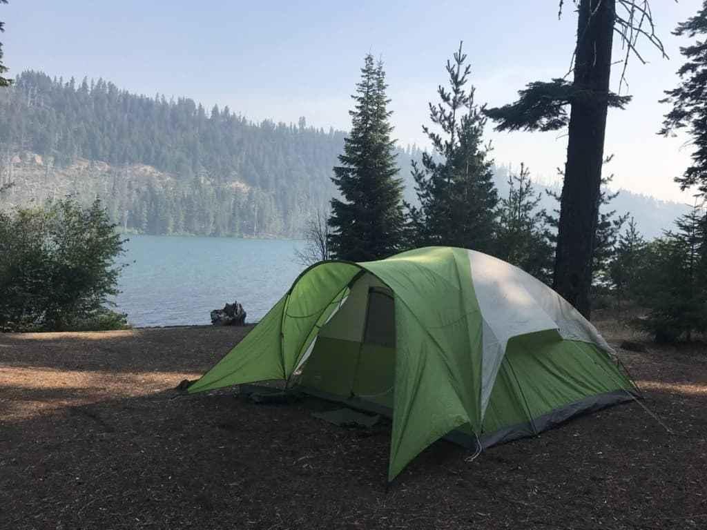 1 chiếc lều cắm trại màu xanh bên hồ
