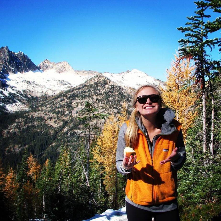 cô gái tóc vàng cầm bánh trên tay phía sau là đỉnh núi tuyết