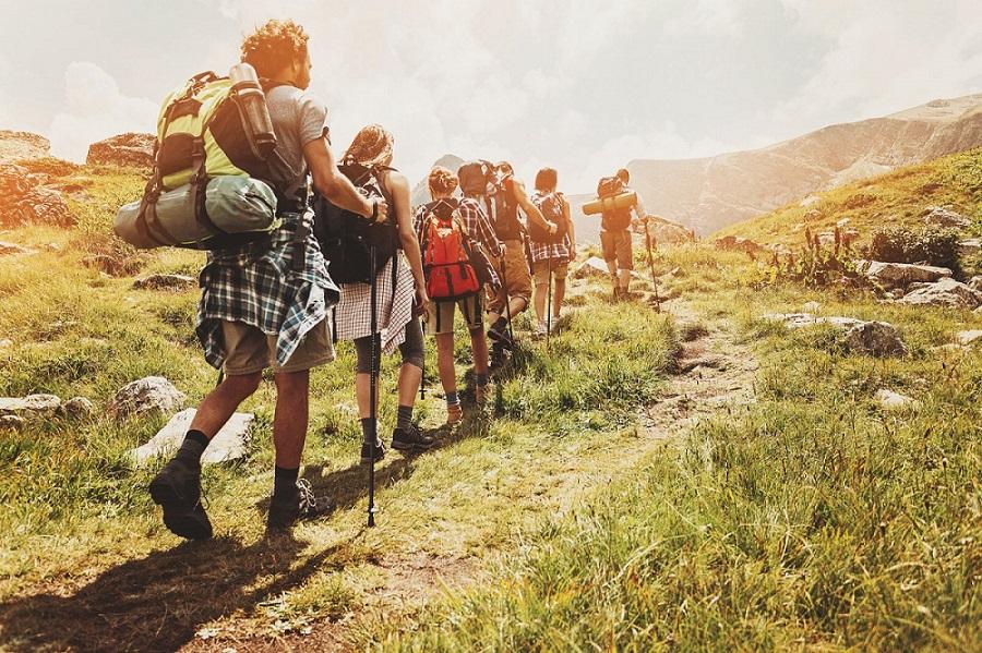 đoàn leo núi di chuyển trên đoạn đường dốc nhiều cỏ hướng lên núi