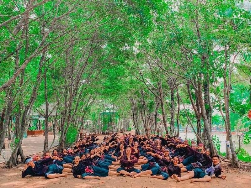 Nhóm bạn cùng nằm tạo dáng dưới hai hàng cây xanh mát