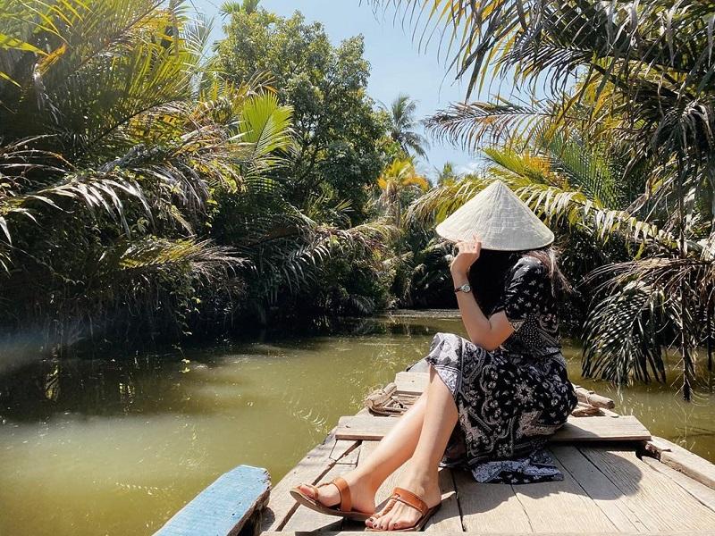 Bạn nữ ngồi trên ghê thuyền qua con kênh
