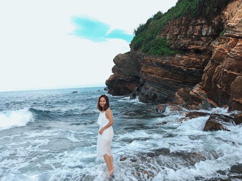 Cô gái mặc đầm trắng vui đùa với sóng ở bãi đá