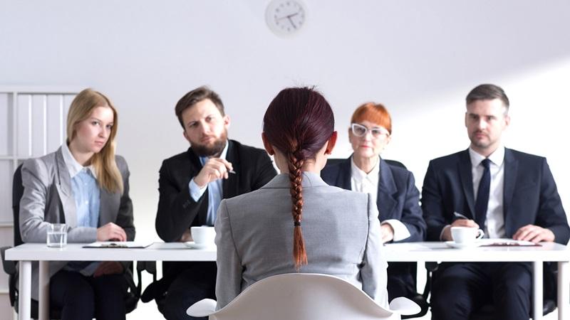 Người được phỏng vấn đang ngồi trước 4 người phỏng vấn mình