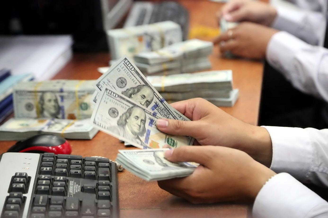 Một người đang đếm tiền đô la Mỹ