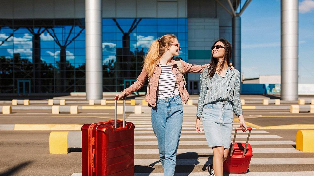 Hai cô mặc kéo vali đang bước đi trên đường phố