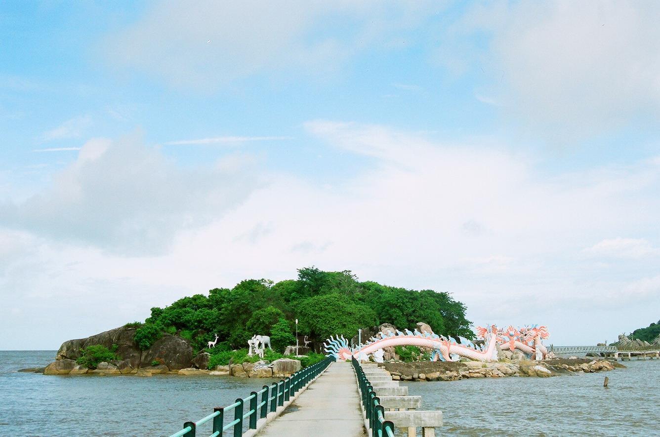 Cây cầu dài nối ddaats liền và hòn đảo rợp bóng cây xanh, 2 bức tượng rồng bay lượn dưới chân đảo