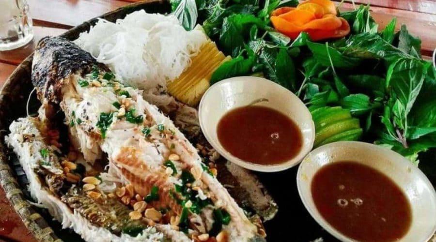 Cá lóc được tách đôi, phần thịt trắng xốp thơm ngon, bên cạnh có 2 bát nước chấm và rau sống xanh non