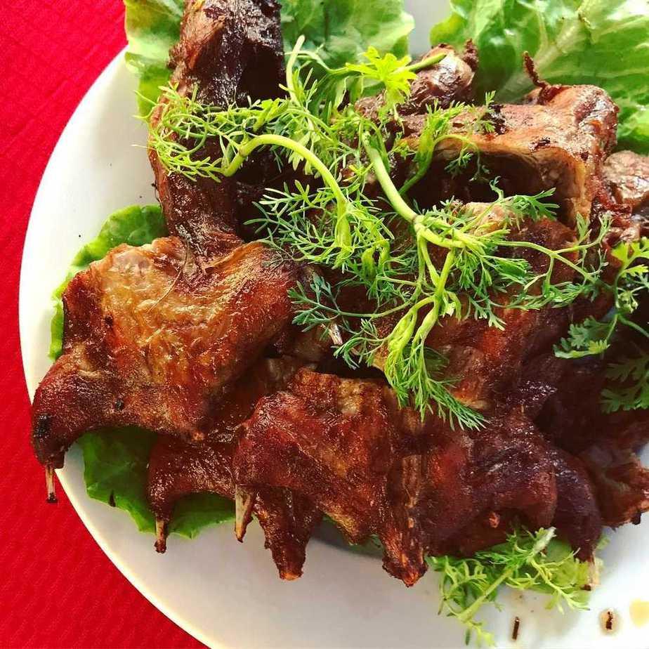 Đĩa thịt chuột đồng chiên vàng giòn, phủ lên trên những cọng rau thơm xanh non