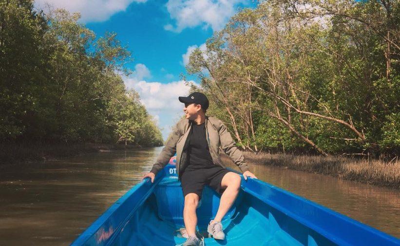 Bạn nam khoác sơmi quần short, đội mũ đen ngồi trên thuyền đi trên con rạch giữa rừng ngập mặn