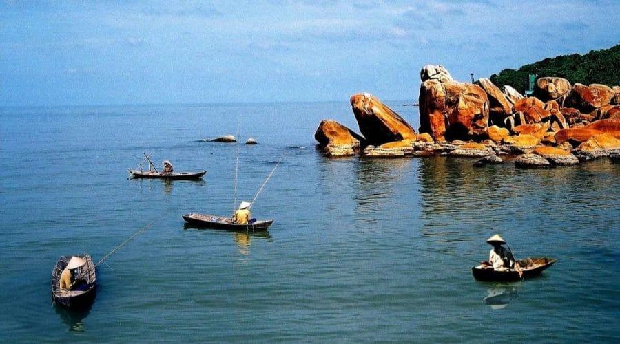 Vùng vịnh nơi hòn đá bạc trong xanh, nhiều thuyền bè di chuyển xung quanh những vách đá