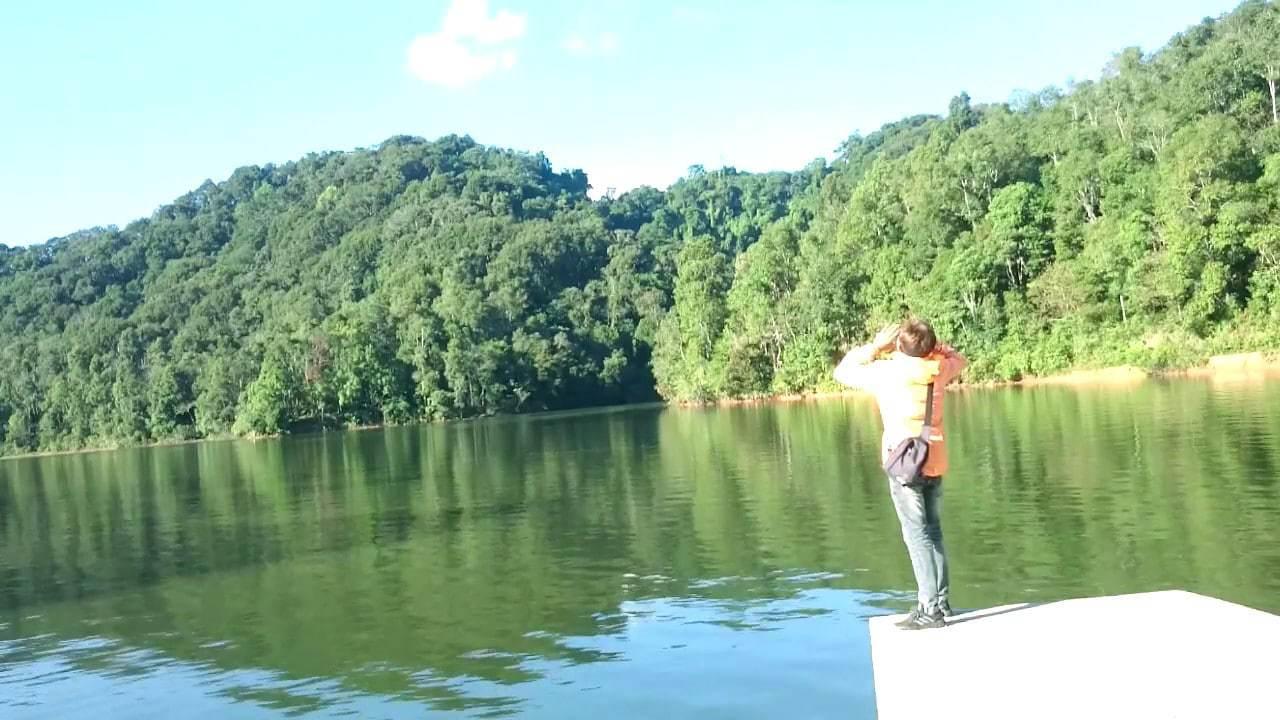 Du khách đứng chụp ảnh trên hồ pá khoang nước trong xanh, xung quanh là rừng cây xanh mát