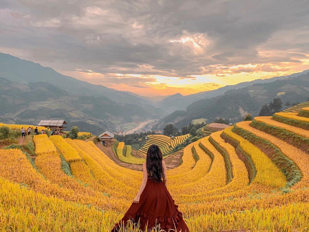Bạn nữ mặc váy dài đỏ chụp ảnh trước cánh đồng lúa bậc thang chín vàng