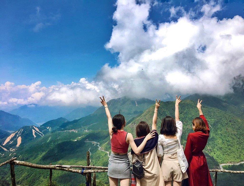 4 bạn nữ check in với khung cảnh trước mặt là đèo ô quy hồ uốn lượn quanh đồi núi xanh ngát