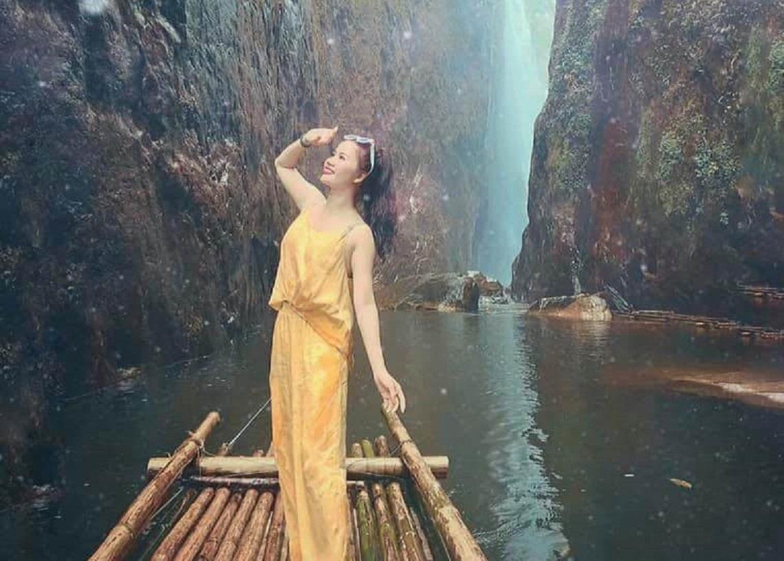 Bạn nữ mặc bộ jumset vàng đứng trên chiếc bè trôi dưới dòng nước giữa 2 khe vách núi đá