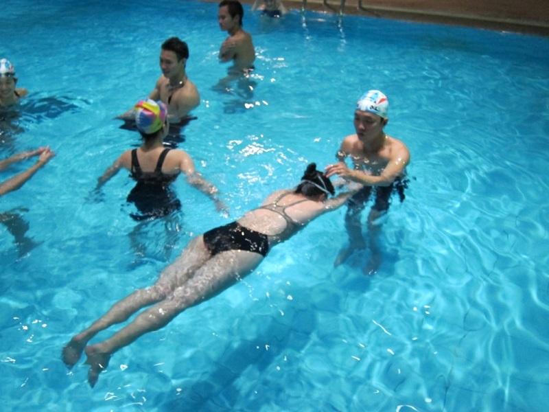Các em nhỏ được HLV dạy bơi trong bể bơi