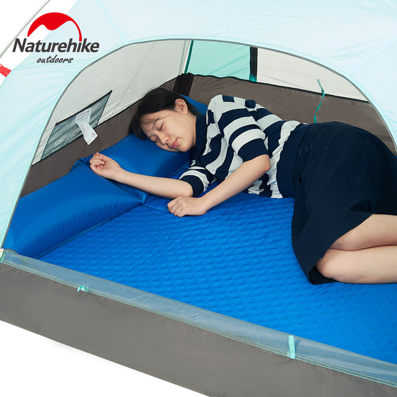 Bạn nữ trải đệm hơi màu xanh trong lều để nằm ngủ
