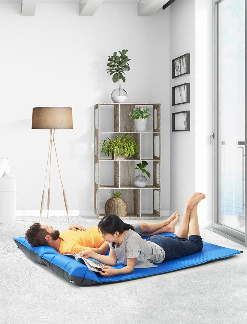 Đôi vợ chồng trải đệm hơi trong nhà để thư giãn cùng nhau
