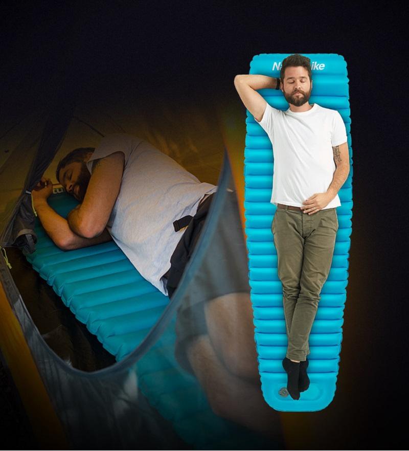 Một người đàn ông đang nằm ngủ trên đệm hơi màu xanh ở trong lều