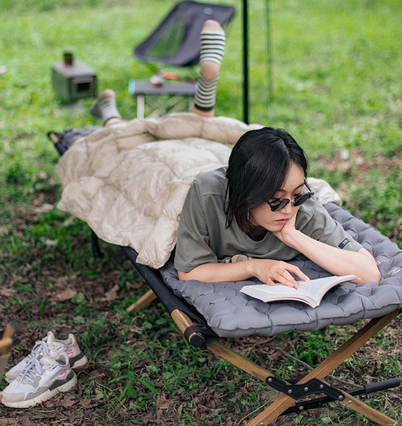 Bạn nữ đọc sách khi nằm trên đệm ngủ