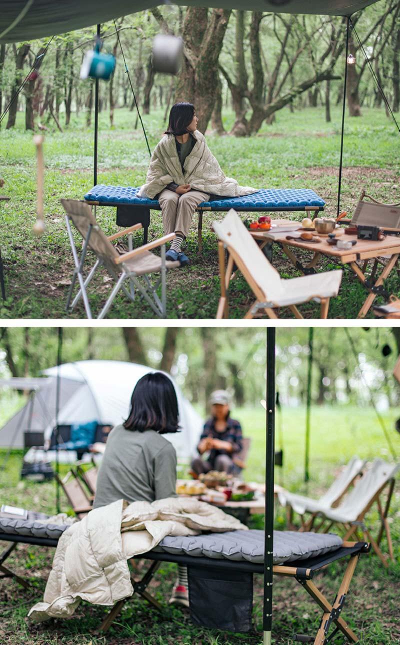 Bạn nữ đang ngồi trên tấm đệm màu xanh ở giường gấp khi đi dã ngoại trong rừng