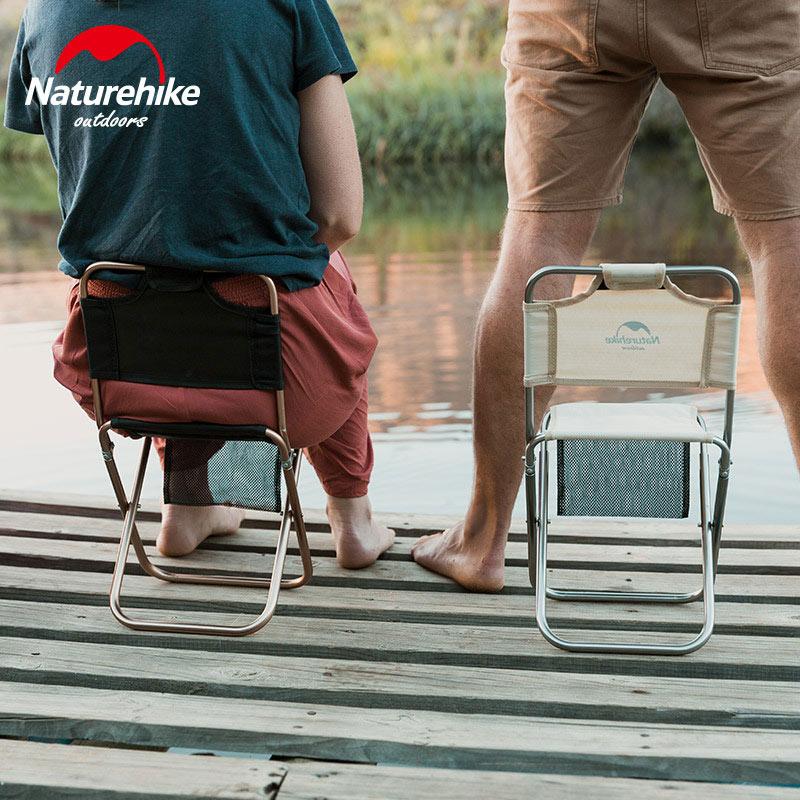 2 người sử dụng ghế xếp câu cá, người bên trái đang ngồi, người bên phải đứng