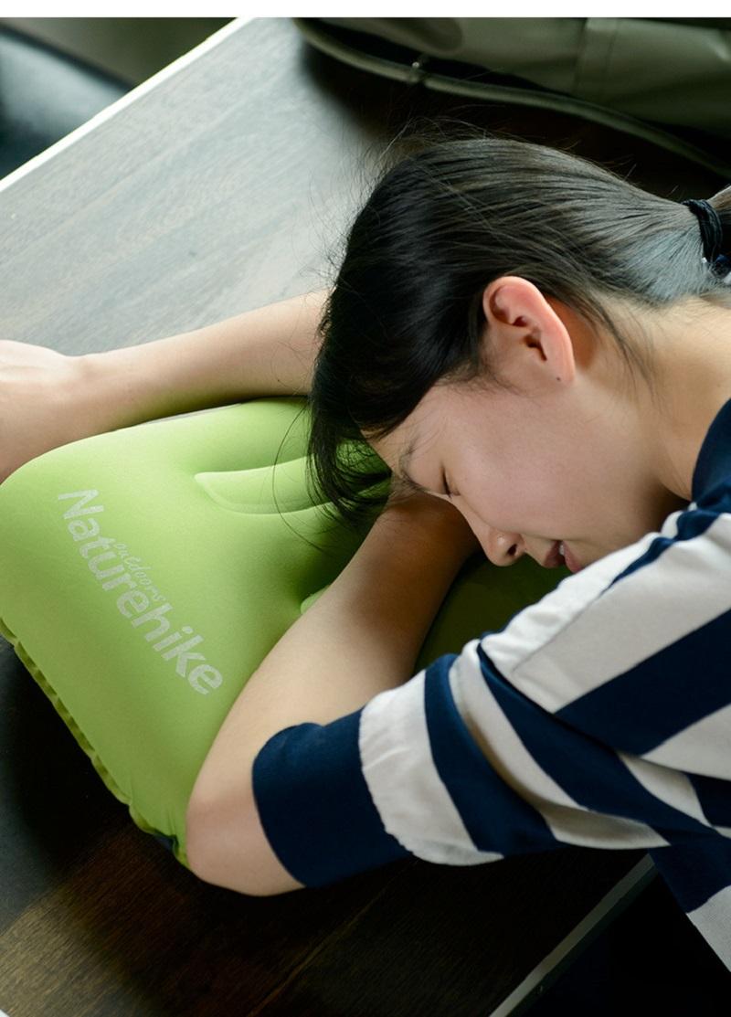 Bạn nữ dùng gối hơi kê đầu trên bàn làm việc để ngủ trưa