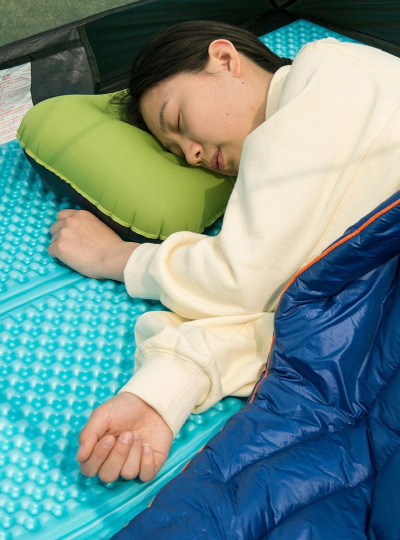 Bạn nữ gối đầu lên gối hơi khi nằm ngủ trên đệm hơi