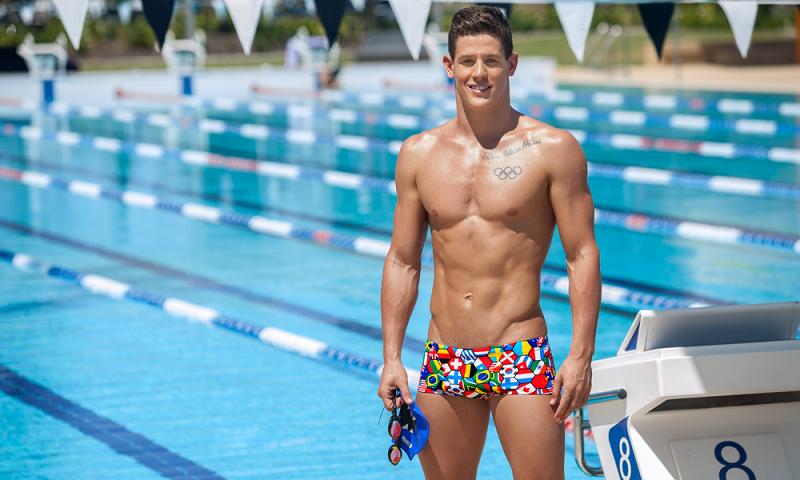 Người đàn ông mặc quần đùi bơi họa tiết đứng bên hồ bơi