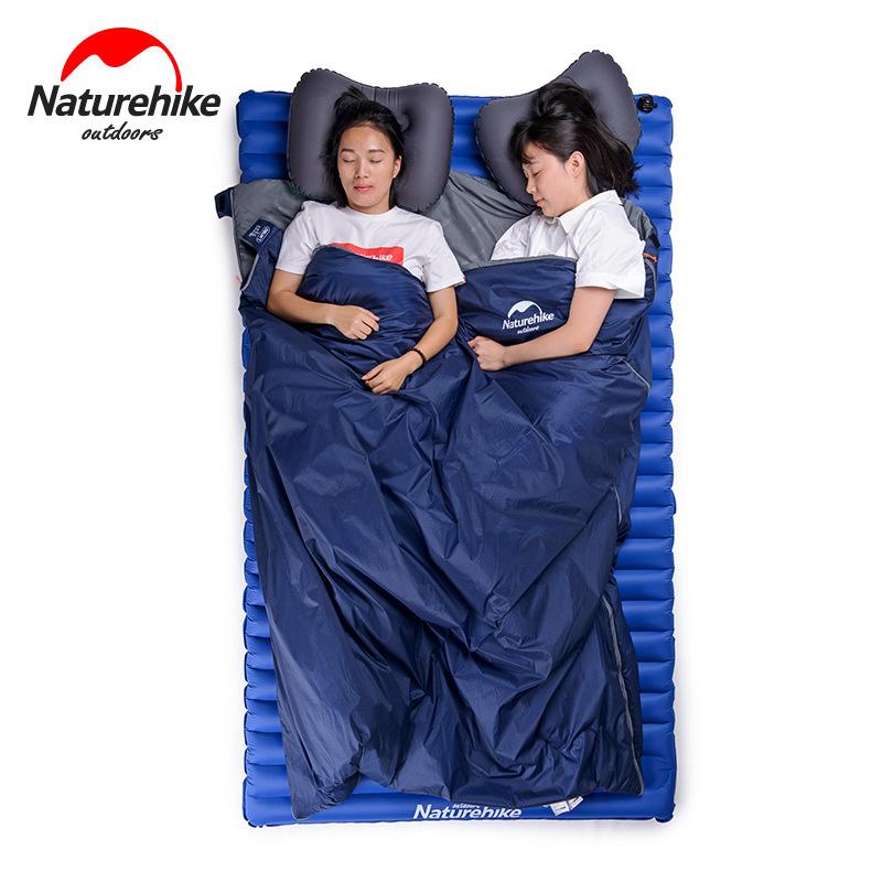 2 bạn nữ đang nằm ngủ trong chiếc túi ngủ đôi