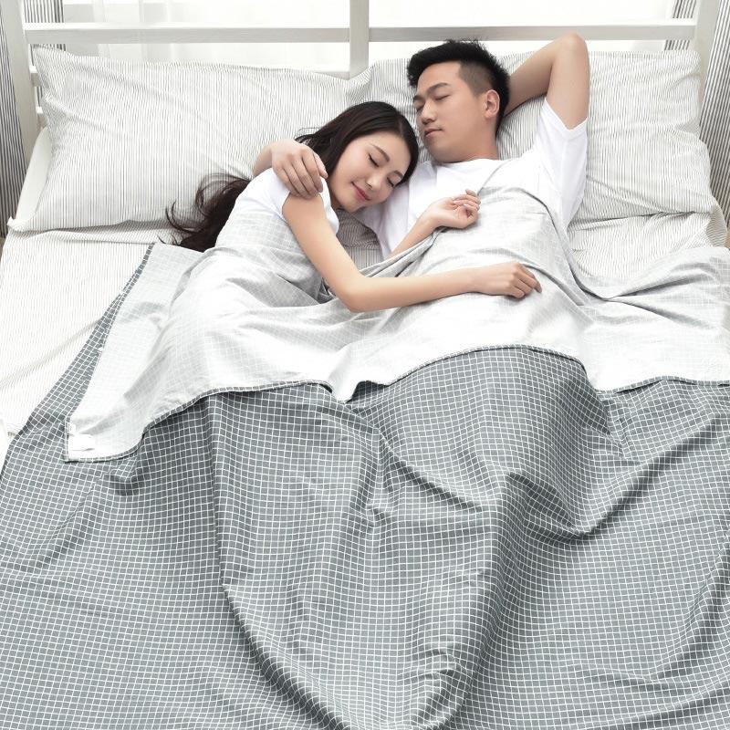 Cặp vợ chồng trẻ ngủ ngon trong túi ngủ xám kẻ caro ở trên giường