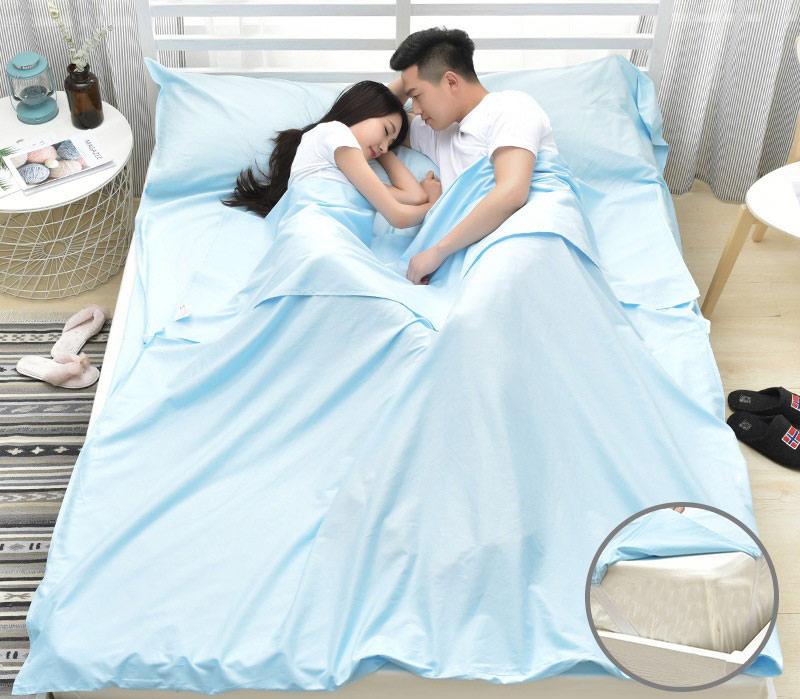 Đôi vợ chồng trẻ nằm ngủ trong túi ngủ xanh nhạt trên giường