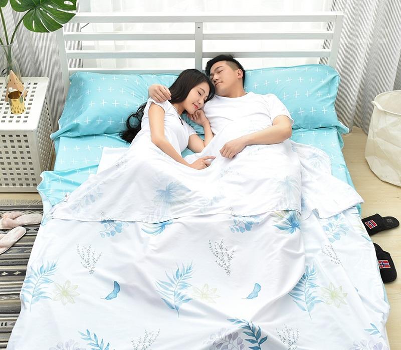 Đôi vợ chồng trẻ nằm ngủ bên nhau gần gũi, thoải mái trong túi ngủ đôi màu trắng hoạ tiết hoa lá