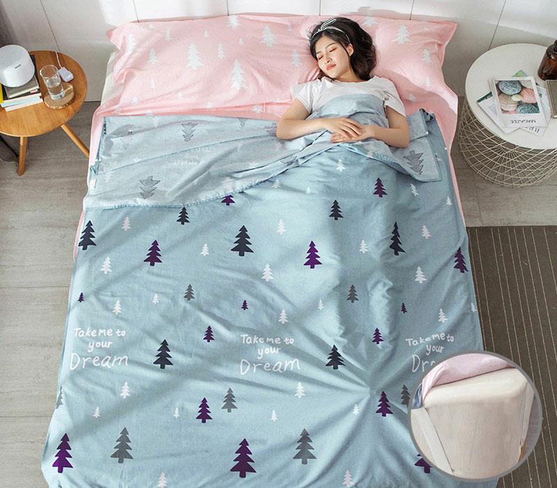 Bạn nữ nằm ngủ trên giường và dùng túi ngủ màu xanh hoạ tiết cây thông như một chiếc chăn mỏng