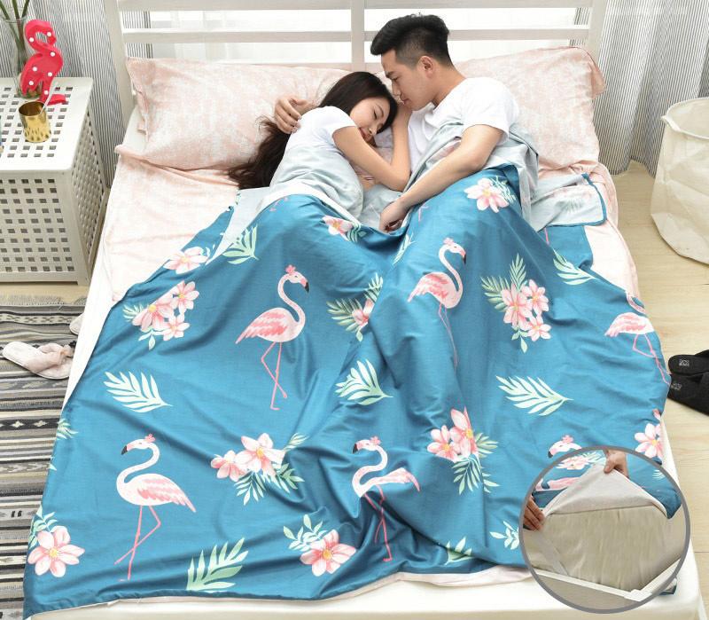 Đôi nam nữ thư giãn cùng nhau với chiếc túi ngủ xanh đậm hoạ tiết cò, hoa trải trên giường