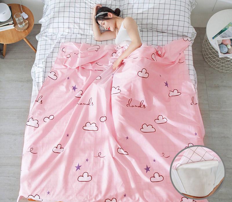 Bạn nữ nằm ngủ trong túi ngủ màu hồng hoạ tiết đám mây trên giường