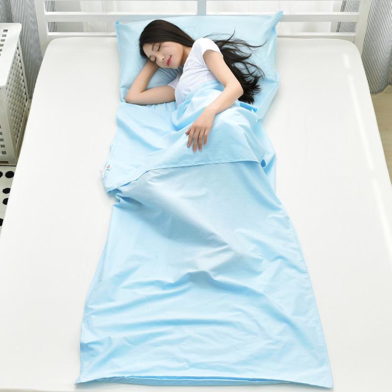 Bạn nữ sử dụng túi ngủ màu xanh dương, nằm trên giường nghỉ ngơi