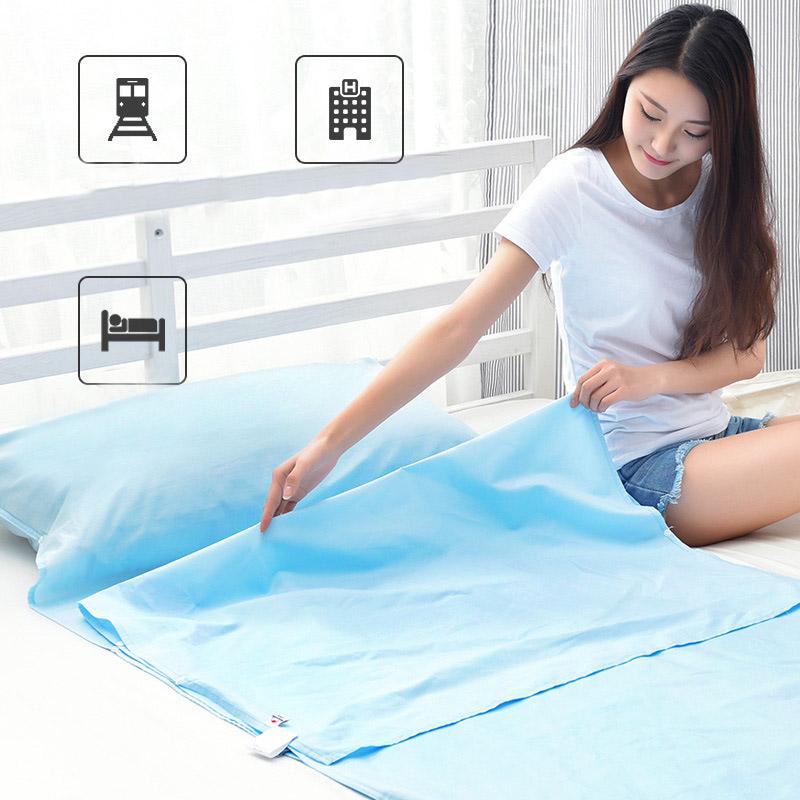 Bạn nữ đang ngồi gấp túi ngủ màu xanh, bên sườn có các khuy bấm