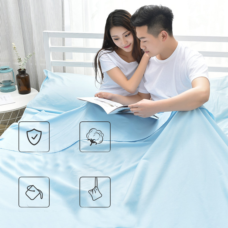 Đôi bạn nam nữ ngồi đọc báo trong túi ngủ màu xanh được làm từ Cotton tự nhiên 100%, thoáng mát và mềm mại.