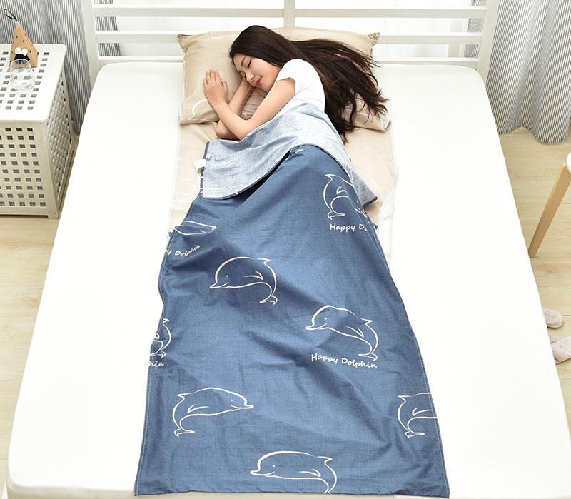 Bạn nữ ngủ trên giường cùng túi ngủ xanh đậm hoạ tiết cá heo