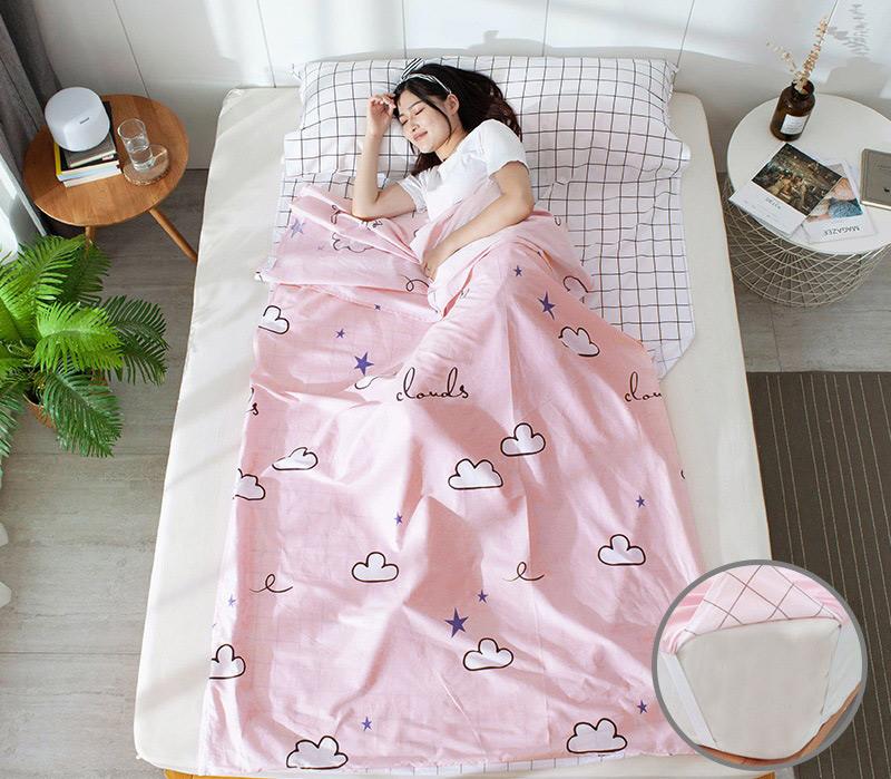 Bạn nữ nằm ngủ trong túi ngủ màu hồng hoạ tiết đám mây