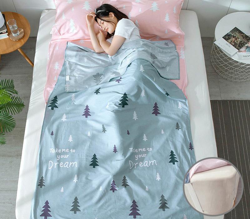 Bạn nữ nằm ngủ trong túi ngủ xanh nhạt hoạ tiết cây thông trải trên giường