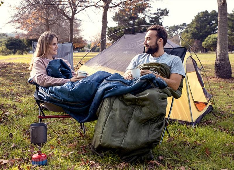 hai người nam và nữ đang dùng túi ngủ Naturehike H150 bên cạnh chiếc lều cắm trại