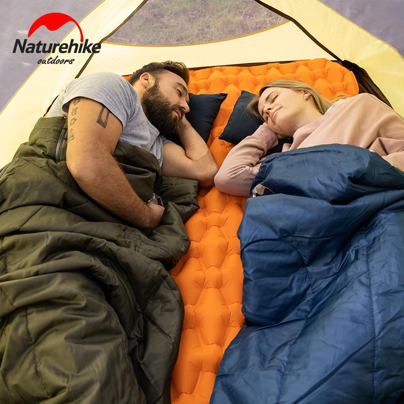 Hai người đang dùng túi ngủ cùng đệm hơi ngủ trong lều
